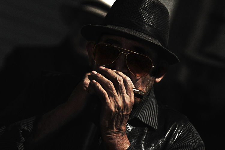 Close-up of mature man playing harmonica