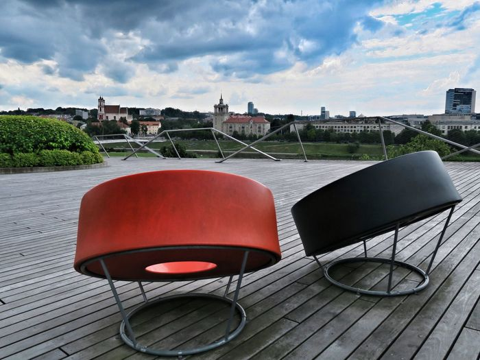 Chairs and table by sidewalk against sky in city