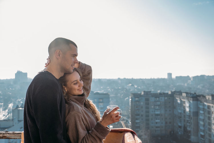 Young couple drinking coffee on the balcony of the apartment in the morning. young happy couple