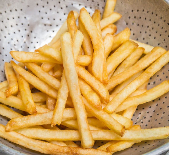 Close up french fries on a wooden background French Fried Snack Yellow Golden Background Food Sauce Portions Plate Salt Ketchup Wooden Spicy Potato Fast Wooden Plate French Fries Fast Food Food And Drink Unhealthy Eating Close-up Fast Food French Fries