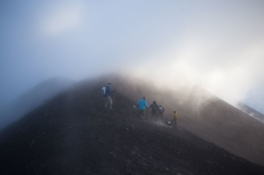 Walking along the ridge towards Mt Fuego from Mt Acatenango, Guatemala. Acatenango Adults Only Adventure Beauty In Nature Cold Temperature Day Fog Fuego Healthy Lifestyle Landscape Mountain Mountain Range Nature Outdoors People Real People Scenics Sky