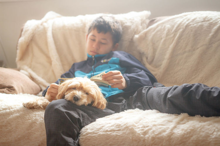 Boy with book sleeping while sitting by dog on sofa at home