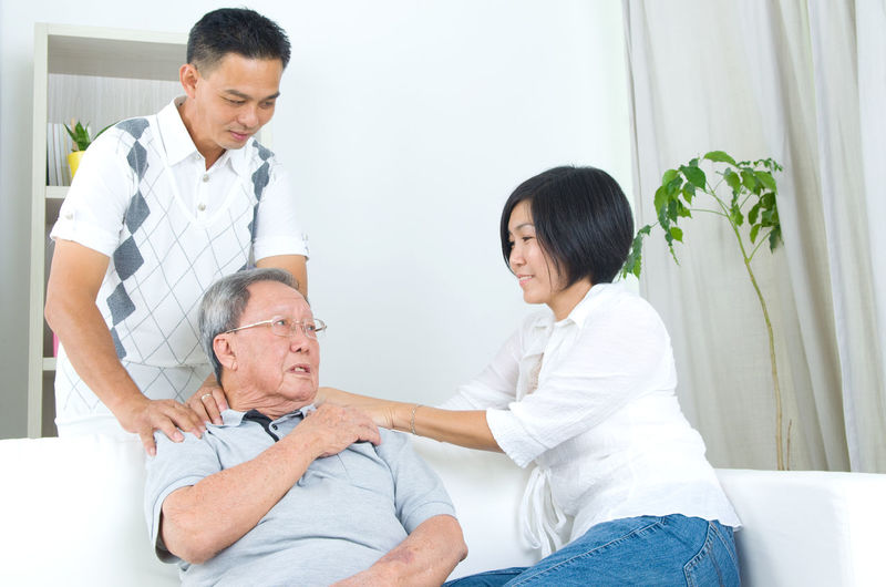 People Giving Shoulder Massage To Father While Sitting On Sofa At Home