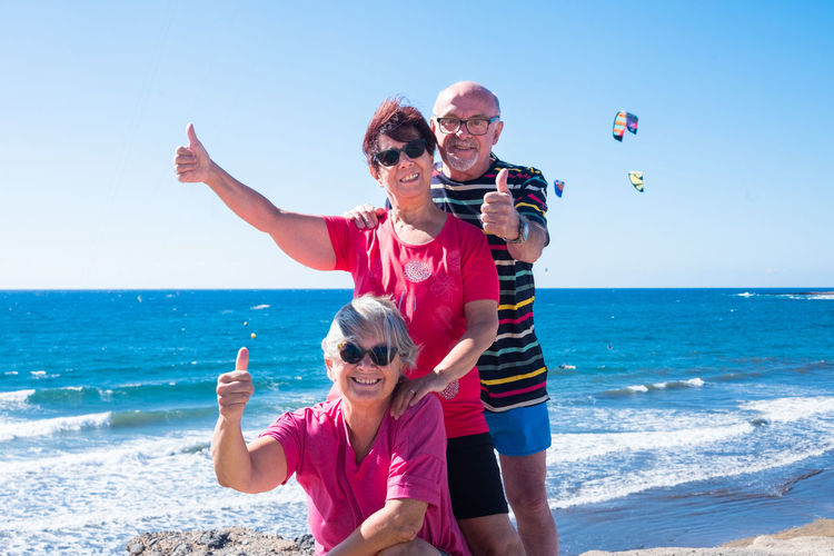 Portrait of smiling senior friends gesturing while at beach against sky