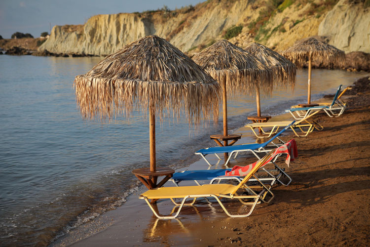 Morning on empty beach Water Beach Thatched Roof Sea Land Chair Lounge Chair Beauty In Nature Roof Nature Umbrella No People Tranquility Scenics - Nature Sand Beach Umbrella Absence Outdoors Scenic View Sunbed Sunbeds And Umbrella Red Sand Morning Rocks