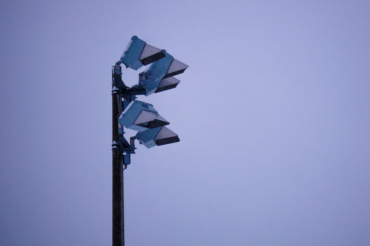 Low angle view of floodlights against clear sky during winter