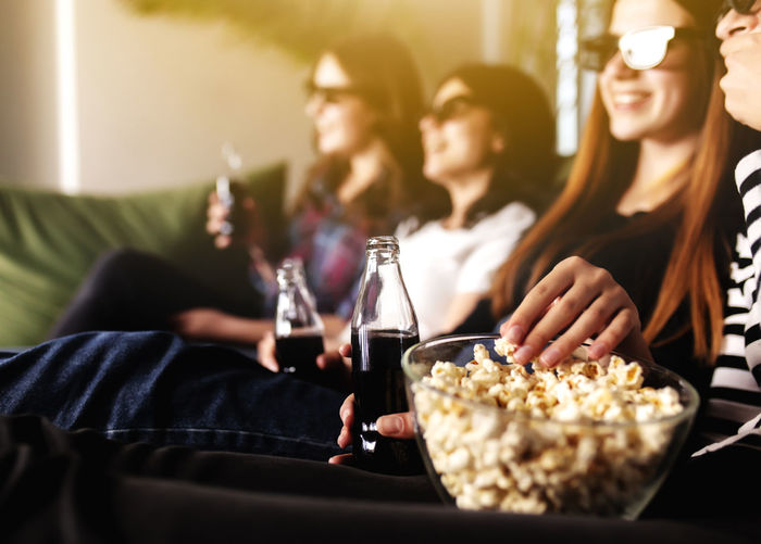 Group of people are watching a movie. friend girls eat popcorn and drink soda