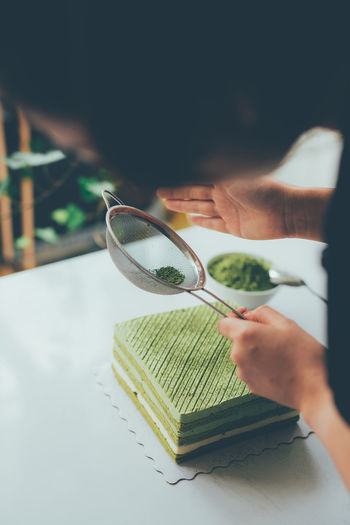 Pour green tea powder over delicious cheesecake Matcha Art And Craft Baked Book Close-up Day Education Finger Green Color Green Tea Hand Holding Human Body Part Human Hand Indoors  Leisure Activity Lifestyles Nature One Person Plant Publication Real People Selective Focus