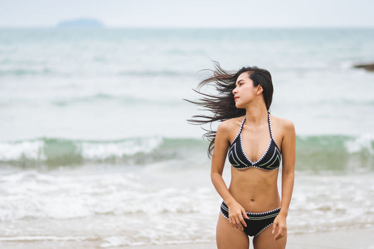 Water Beach Sea Land One Person Young Adult Three Quarter Length Beauty Young Women Standing Beautiful Woman Real People Leisure Activity Clothing Focus On Foreground Hairstyle Nature Hair Tousled Hair Horizon Over Water Outdoors