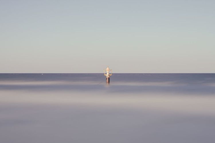 Man standing in sea against clear sky