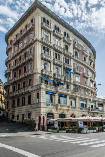 An old apartment building along the coast of Naples, Italy. Apartment Buildings Naples Naples, Italy Apartment Architecture Building Building Exterior Built Structure City Cloud - Sky Day Direction Juliet Balcony Low Angle View Nature No People Outdoors Residential District Restaraunt Road Sky Street Sunlight Transportation Window