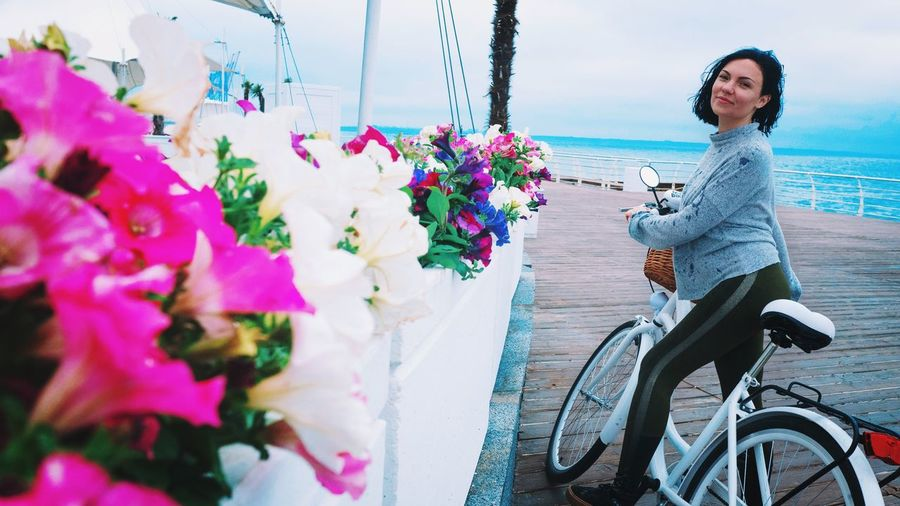 Portrait Of Woman With Bicycle Standing By Flowers At Pier