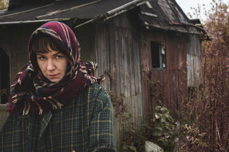 A grumpy woman in a warm head scarf and coat stands against the backdrop of an old abandoned house.
