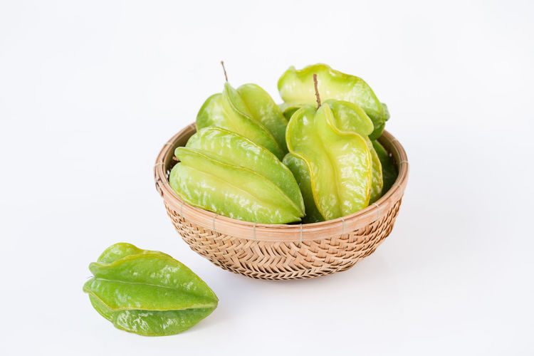 Close-up of fruits in basket against white background