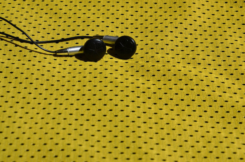 Close-up of in-ear headphones on yellow textile