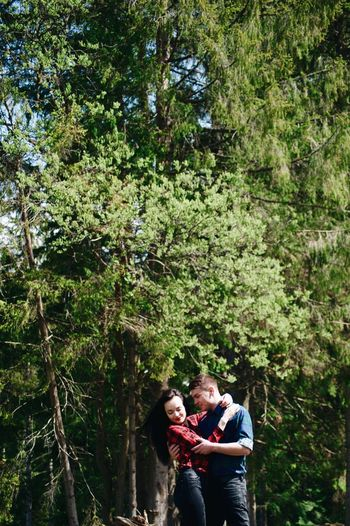 Loving Young Couple Standing Against Trees In Forest