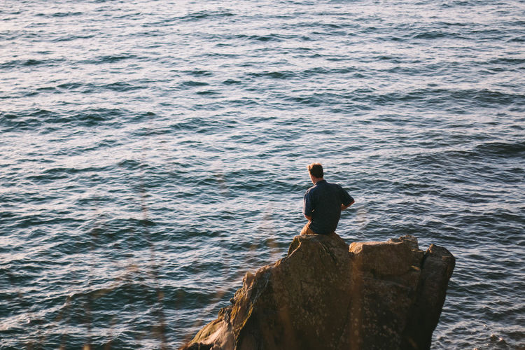 High angle view of man on rock against sea