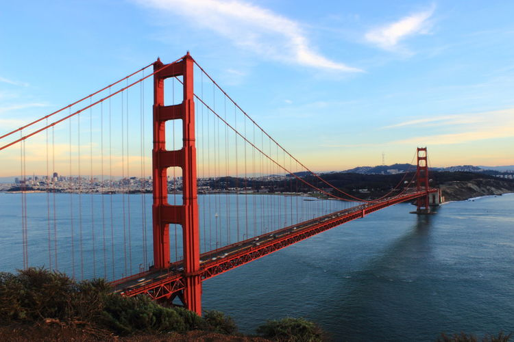 Golden gate bridge over sea against cloudy sky