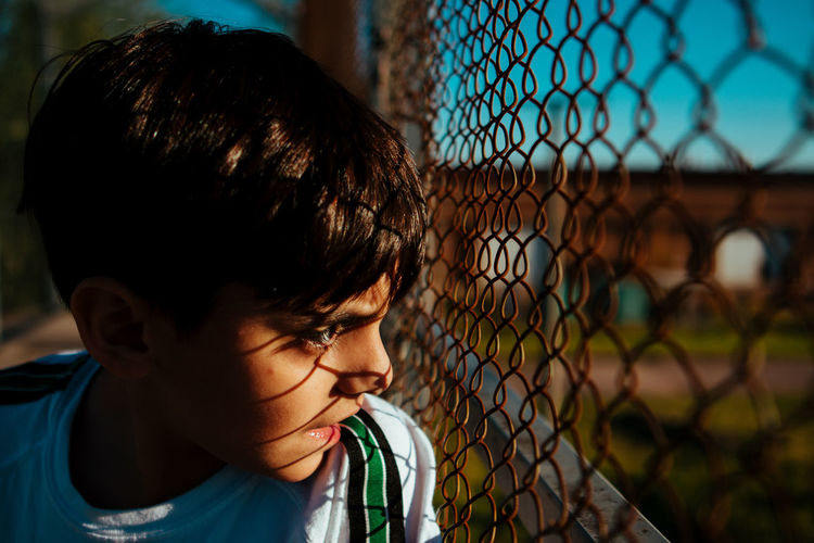 Close-up f boy looking through chainlink fence