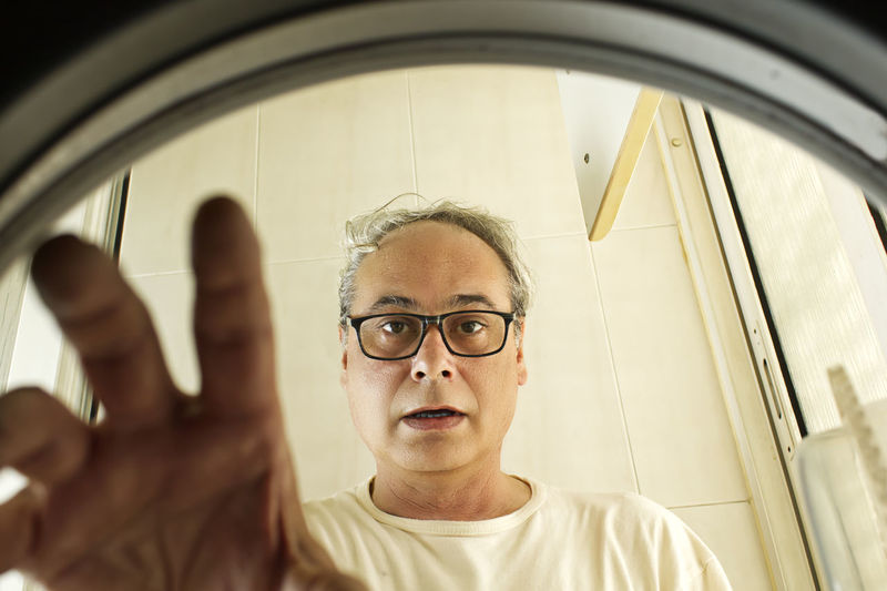 Mature man taking clothes out of the washing machine seen from inside