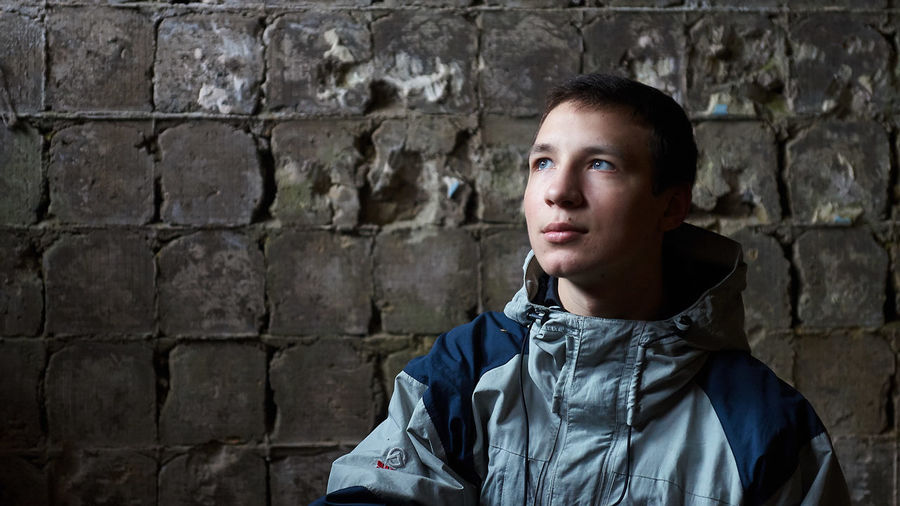 Young man looking up while standing against wall
