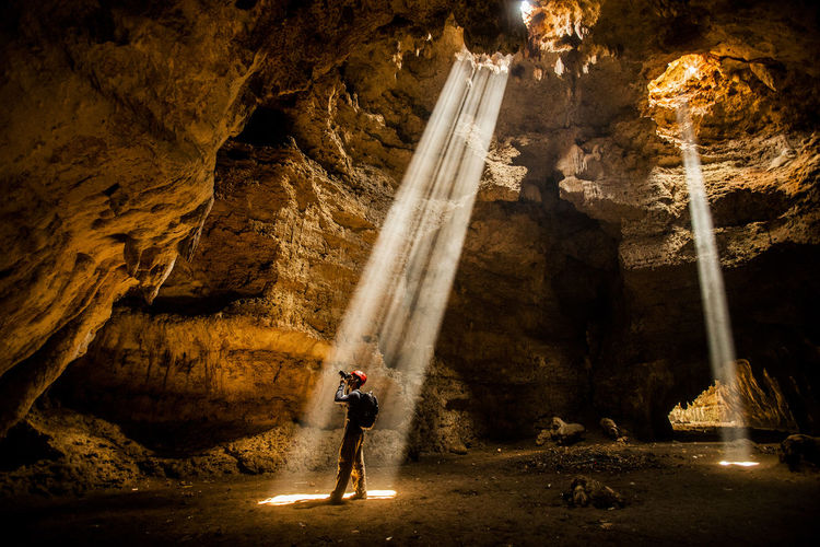 Side View Of Man Photographing While Standing In Caves