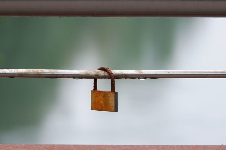 A closed padlock on a steel bar