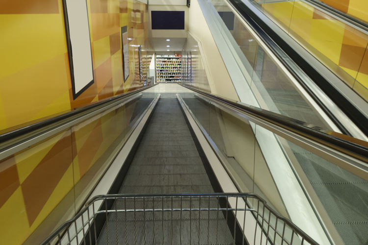 Shopping cart going down Advertisement Posters Conveyor Belt Shopping Shopping Cart Supermarket Advertisement Architecture Billboard Blank Cart Colorful Escalator Illuminated Indoors  Mall Modern No People Railing Shopping Mall The Way Forward