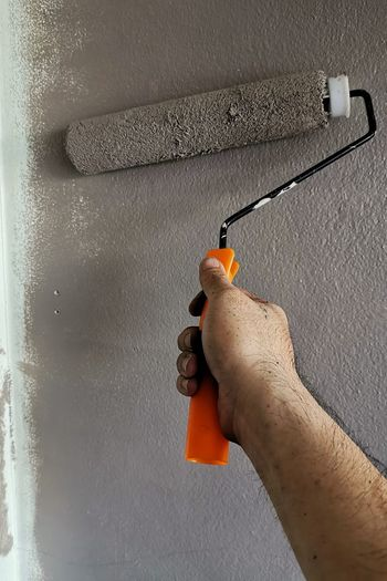 Close-up of man holding stick against orange wall