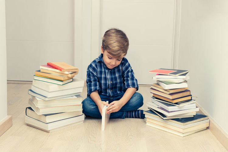 Rear view of boy sitting on books