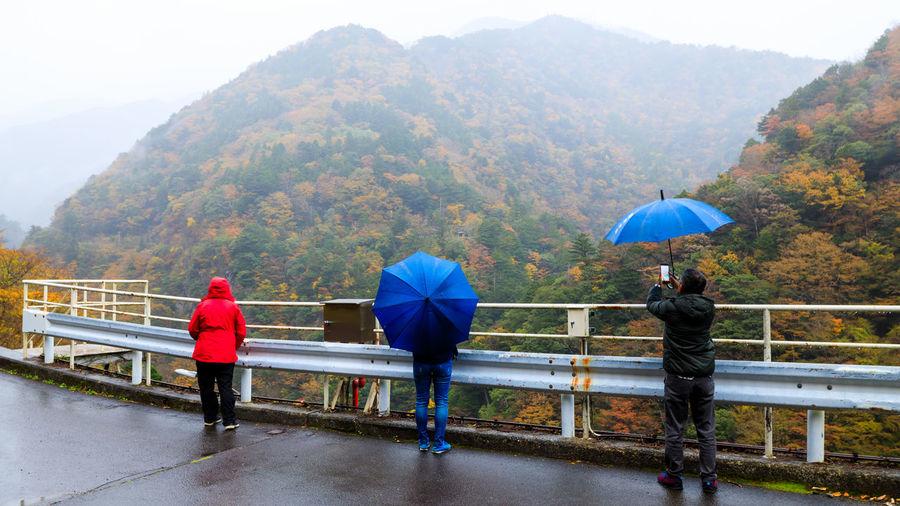 Rear view of people on footbridge in rainy season