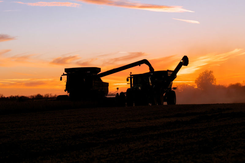 Silhouette combine harvester on land against sky during sunset