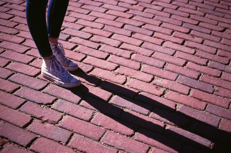 Legs cast a shadow on a brick street