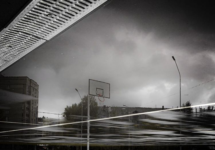 Low angle view of wet street against sky