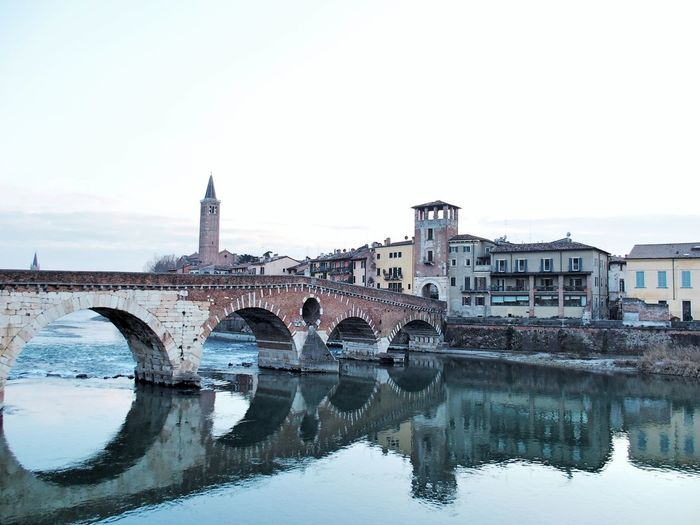 Ponte pietra reflecting in adige river against sky