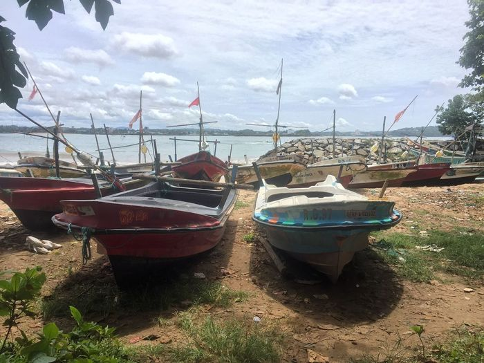 Boats moored at beach against sky
