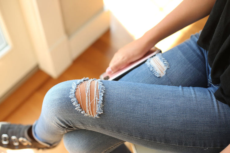 Low section of teenage girl sitting on seat at home