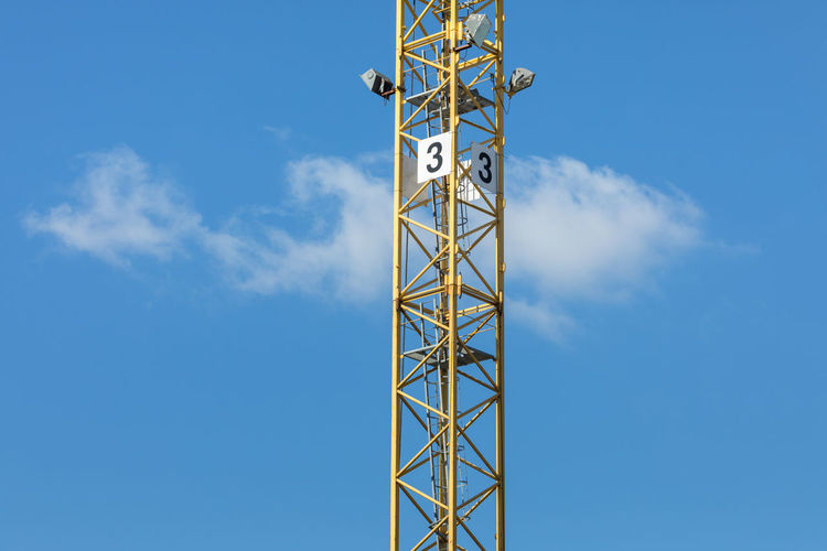 Low Angle View Of Number 3 On Crane Against Blue Sky