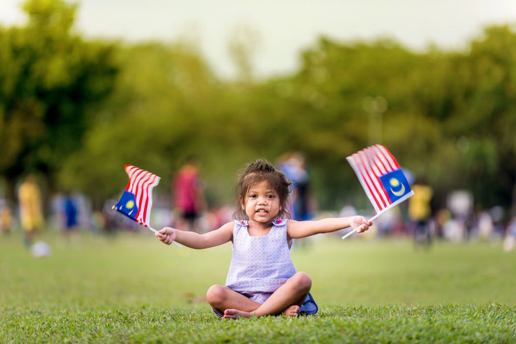 Portrait of cute girl sitting with malaysian flags on grass at park