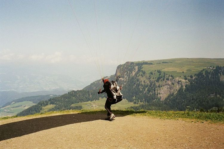Man Holding Ropes While Paragliding On Mountain Against Sky