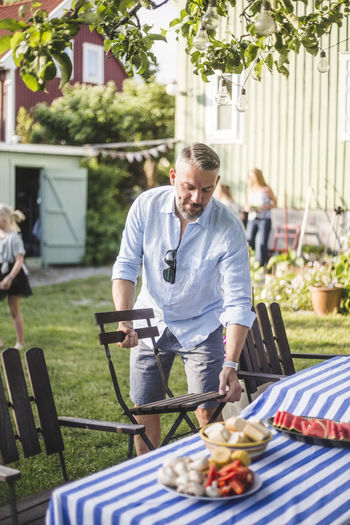 Full length of man preparing food on barbecue grill in yard