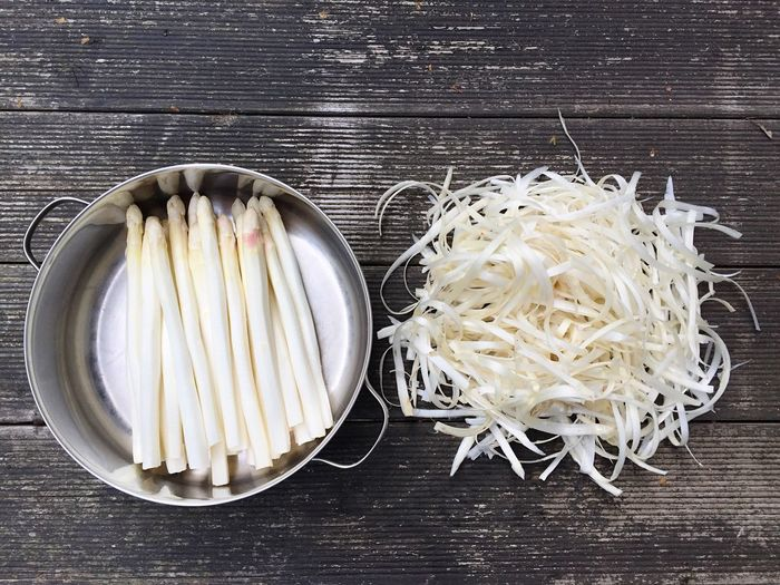 White asparagus in container on wooden wall