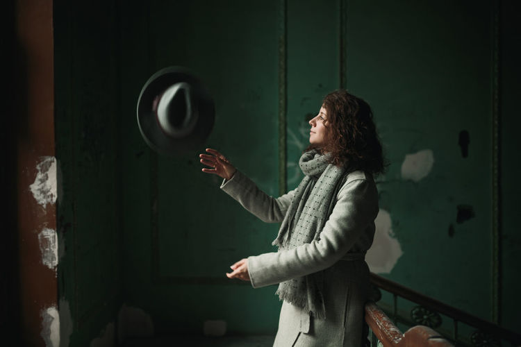 A young girl with wavy hair in a gray coat and scarf throws her gray hat up and smiles. Girl in an old house with green walls and stairs. Smile Green Color Hat Wall Coat Curly Hair Girl Gray Old Buildings Portrait Real People Scarf Stair Vintage Young Women