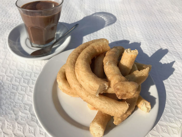 Churro, fried dough snack, with hot chocolate Breakfast Churro Close-up Dessert Drink Food Food And Drink Freshness Fried Dough Hot Chocolate Indulgence No People Plate Ready-to-eat Serving Size Snack Snack Table