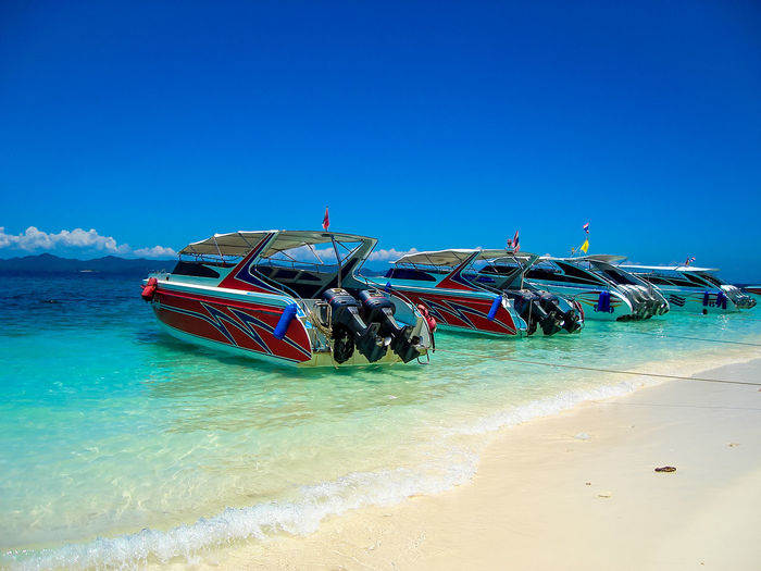 Speed boats at a beach in Phuket, Thailand Beach Beauty In Nature Blue Clear Sky Day Fast Island Nature Nautical Vessel No People Outdoors Sand Scenics Sea Sea And Sky Sightseeing Tour Sky Speed Boats Sunlight Tourism Transportation Vacation Water