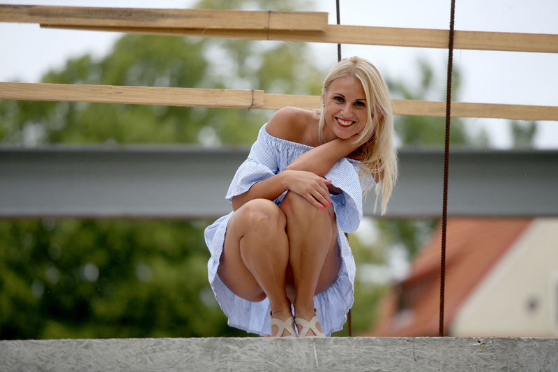 Portrait of young woman against railing