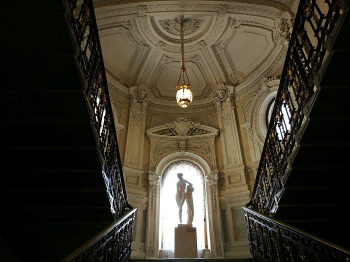 Low angle view of statues and pendant light in historic building