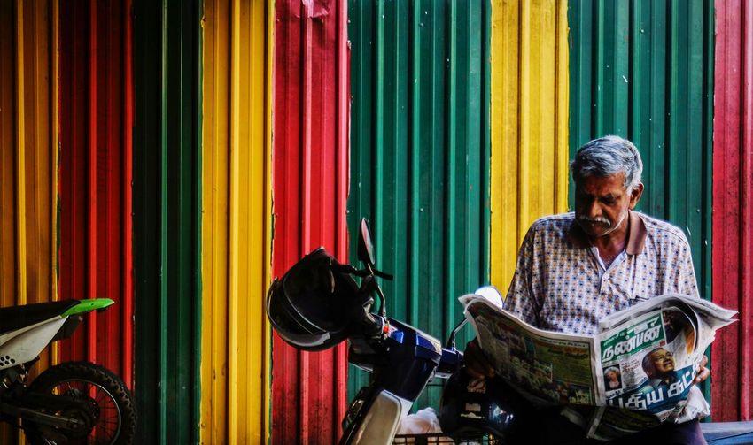 Senior man reading newspaper while sitting on motorcycle