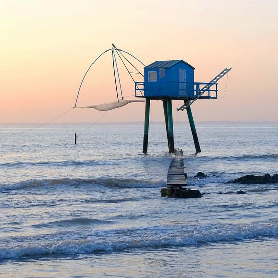Lifeguard hut on sea against sky during sunset