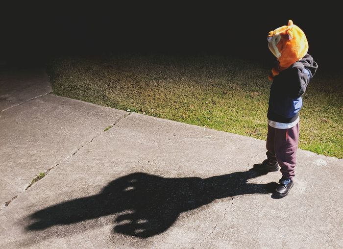High angle view of boy standing on footpath at night
